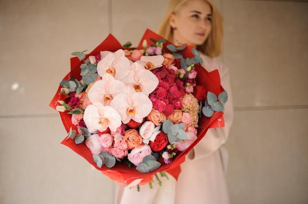 Leuk meisje met boeket rozen en irissen