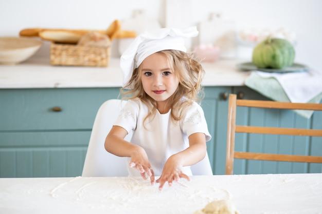 Leuk meisje met chef-kok eenvormig in keuken