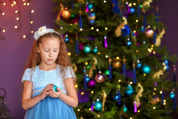 Leuk meisje met de giftdoos van de balholding dichtbij kerstboom