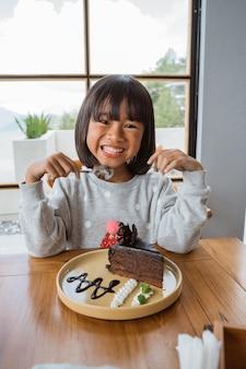 Leuk meisje met dessertvoedsel klaar om te eten