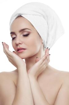 Leuk meisje met donkere wenkbrauwen en naakte schouders, met een witte handdoek op het hoofd, hand vasthoudend met manicure, naar beneden kijkend, lichte naakte make-up, schoonheidsfoto, model met goed getoonde sleutelbeenderen.
