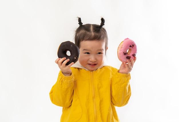 Leuk meisje met donuts op een witte achtergrond