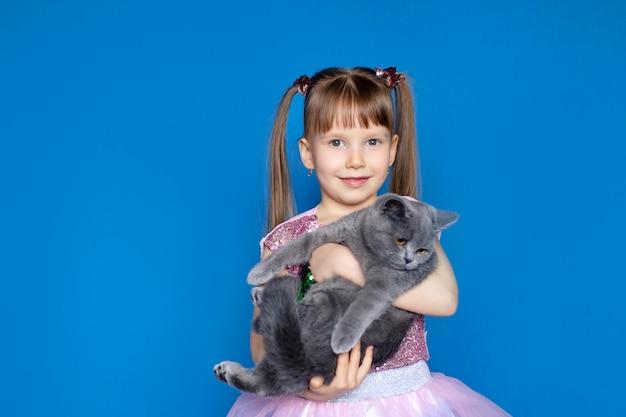 Leuk meisje met een grijze schotse kitten in haar armen.