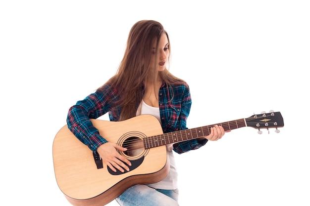 Leuk meisje met gitaar in handen glimlachend geïsoleerd op witte achtergrond