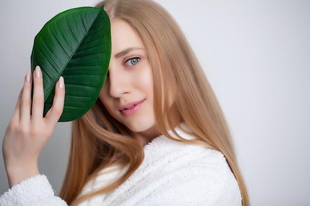 Leuk meisje met groen blad na het nemen van een douche