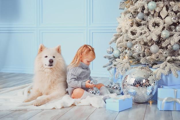 Leuk meisje met haar hond die kerstboom thuis versieren.