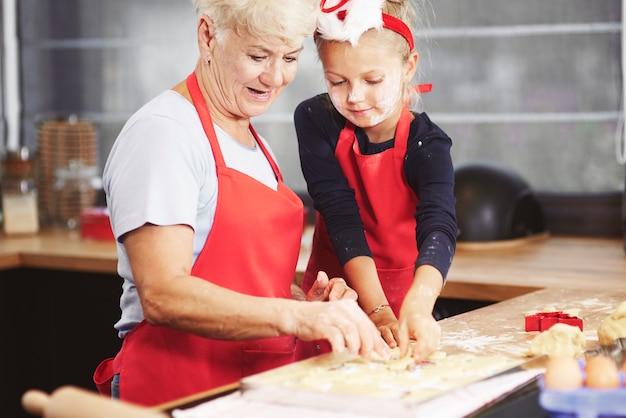 Leuk meisje met haar oma die deeg maakt
