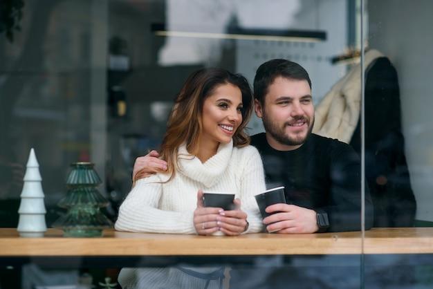 Leuk meisje met haar vriendje zit in een café en het drinken van hete geurende koffie terwijl buiten koud weer is. liefde en romantiek.