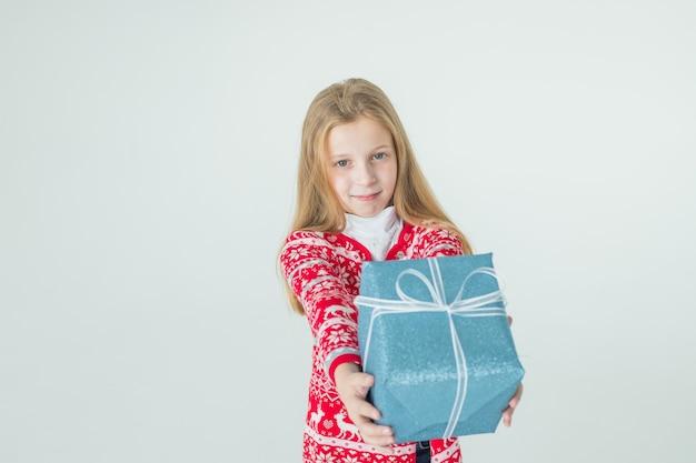 Leuk meisje met kerstcadeau. schattige jongen, kind draagt rode gebreide noordse trui met cadeau