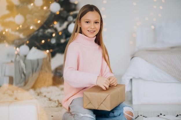 Leuk meisje met kerstcadeautjes door kerstboom