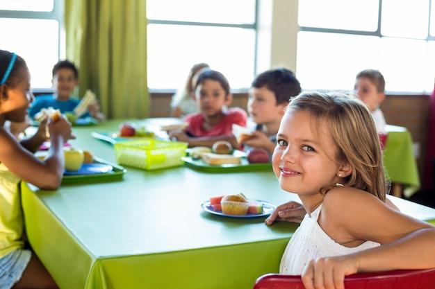Leuk meisje met klasgenoten die maaltijd hebben