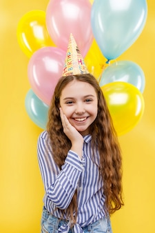 Leuk meisje met kleurrijke opblaasbare ballonnen geïsoleerd op een geel