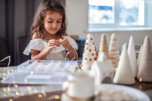 Leuk meisje met krullend haar is met de hand bezig met het maken en decoreren van papieren kegel kerstboom met knopen, garen en kerstverlichting.