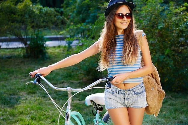 Leuk meisje met krullend haar met hoed, top en korte broek staan met fiets in park, reizen, portret, glimlachen.