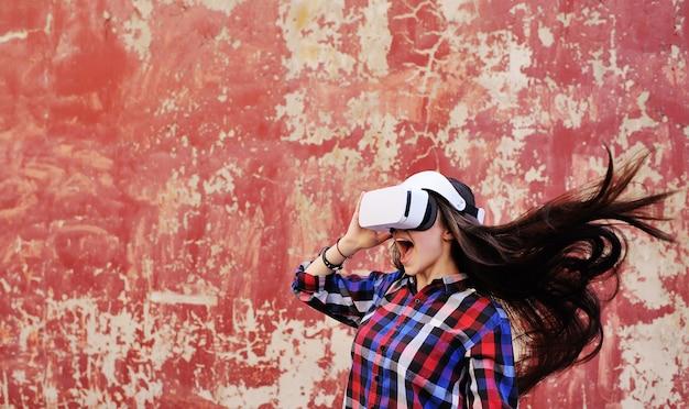 Leuk meisje met lang haar in vr-glazen in plaidoverhemd op de rode achtergrond van de grungemuur.