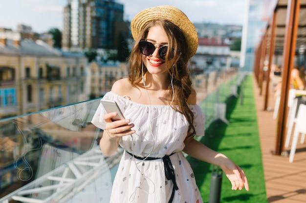 Leuk meisje met lang haar in zonnebril staat op het terras. ze draagt een witte jurk met blote schouders, rode lippenstift en hoed. ze hoort muziek via een koptelefoon.