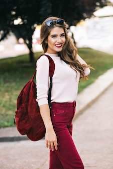 Leuk meisje met lang haar lacht in stadspark. ze heeft marsala-kleur op haar spullen. ze ziet er genoten uit.