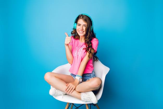 Leuk meisje met lang krullend haar koelen in stoel op blauwe achtergrond. ze draagt een korte broek, een roze t-shirt, witte sneakers. ze luistert naar muziek, houdt de benen gekruist op de stoel en lacht naar de camera.
