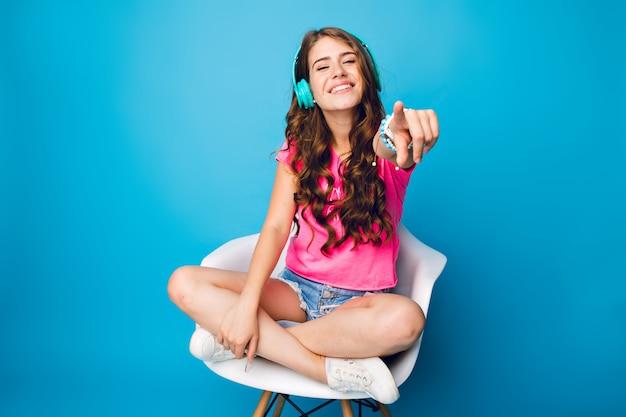 Leuk meisje met lang krullend haar, luisteren naar muziek in stoel op blauwe achtergrond. ze draagt een korte broek, een roze t-shirt, witte sneakers. ze houdt de benen gekruist op de stoel en strekt haar hand uit naar de camera.