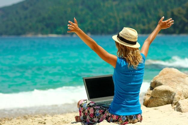Leuk meisje met laptop aan zee concept werk