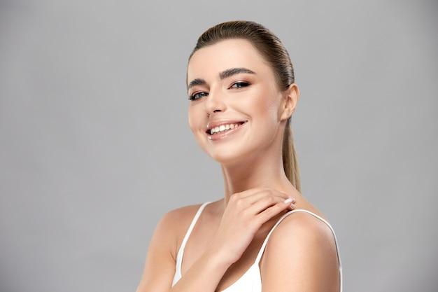 Leuk meisje met naakt mua glimlachend naar camera in grijze muur, mooie vrouw met een gezonde huid aanraken van haar nek, gekleed in een wit overhemd