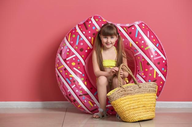 Leuk meisje met opblaasbare ring en strandtas in de buurt van kleurenmuur
