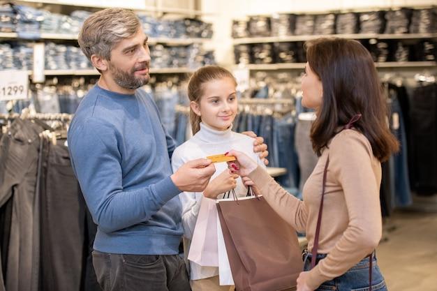 Leuk meisje met paperbags kijken naar haar moeder die creditcard uit de hand van een casual man neemt terwijl ze gaat betalen voor kleding die ze hebben gekocht