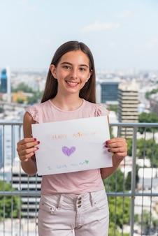 Leuk meisje met papier met happy mothers day inscriptie