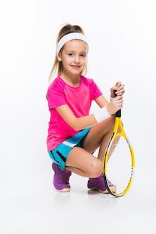 Leuk meisje met tennisracket in haar handen op wit