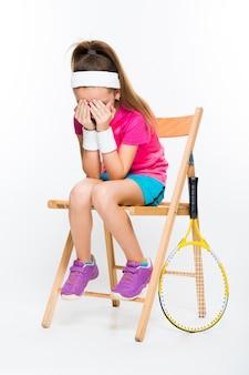 Leuk meisje met tennisracket op wit