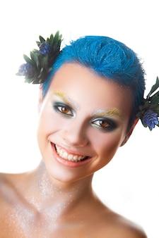Leuk meisje met veelkleurige make-up en kort blauw kapsel glimlachend studio-opname geïsoleerd