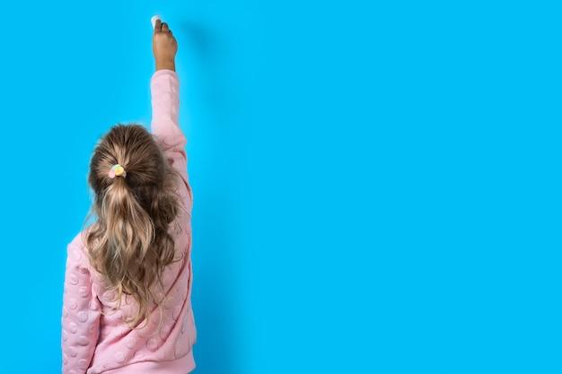 Leuk meisje met wit krijt op een blauw.
