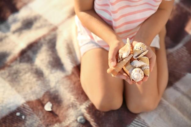 Leuk meisje met zeeschelpen op strand
