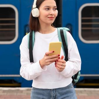 Leuk meisje op het treinstation, luisteren naar muziek
