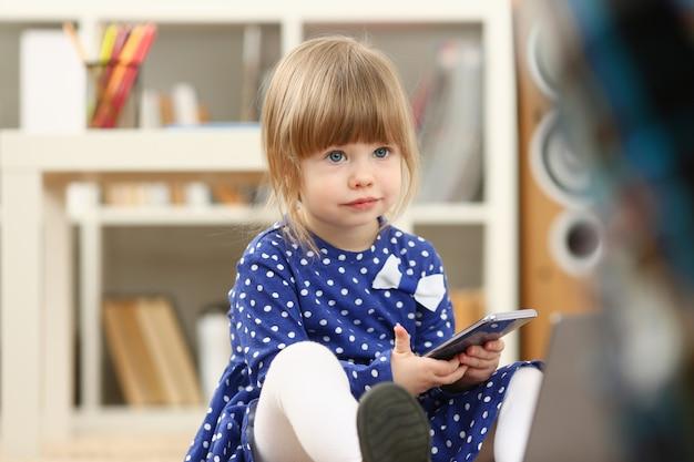 Leuk meisje op het vloertapijt die cellphone gebruiken