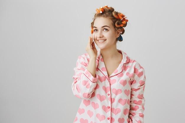 Leuk meisje opstijgen make-up voor het slapen met wattenschijfje, haarkrulspelden en pyjama dragen