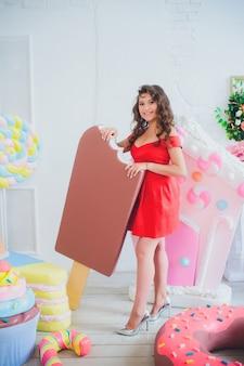 Leuk meisje poseren met roze donuts, gek rond, dessert, slecht eten, kijkt in het gat in de donut, houdt donuts bij de ogen