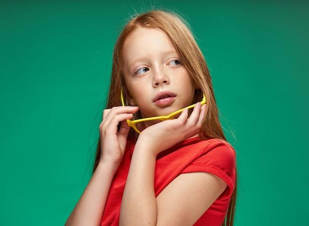 Leuk meisje rood haar bril onderwijs school groene achtergrond. hoge kwaliteit foto
