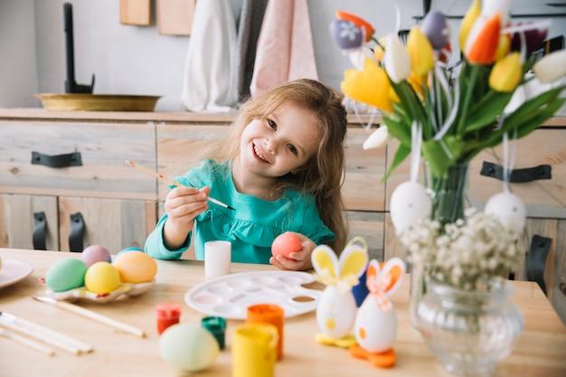 Leuk meisje schilderij eieren voor pasen aan tafel
