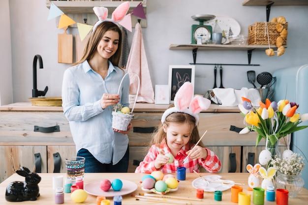 Leuk meisje schilderij van eieren voor pasen in de buurt van moeder met mandje