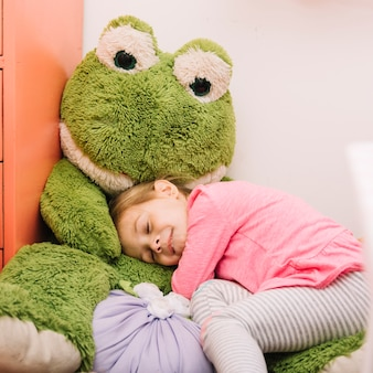 Leuk meisje slaapt met zacht stuk speelgoed