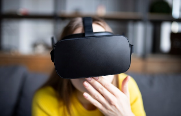 Leuk meisje speelt het spel op de console. gelukkig jonge vrouw met behulp van een virtual reality-headset