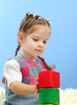 Leuk meisje speelt met veelkleurige blokken, op blauw