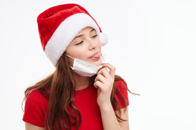 Leuk meisje tong uitsteekt medische masker rode t-shirt kerst. hoge kwaliteit foto