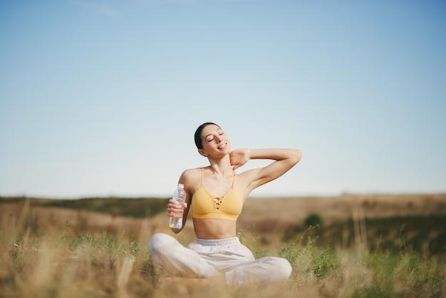 Leuk meisje training op blauwe hemel in een veld