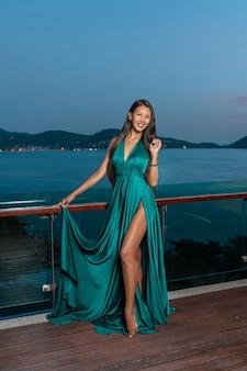 Leuk meisje van gemengd ras poseren op het terras in een jurk in de kleuren van de zeegolf met de zoom van de jurk in haar hand