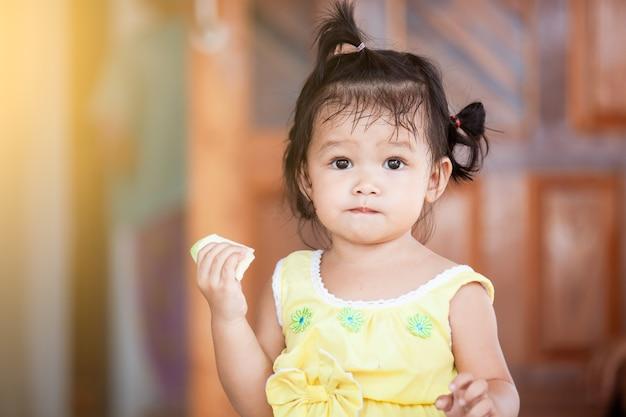 Leuk meisje van het baby aziatisch kind die mango eten