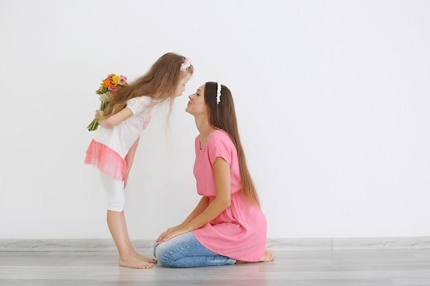 Leuk meisje verbergt bloemen en moeder op lichte achtergrond