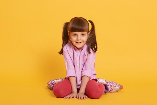Leuk meisje zit in rollen in shirt en leggins en glimlacht