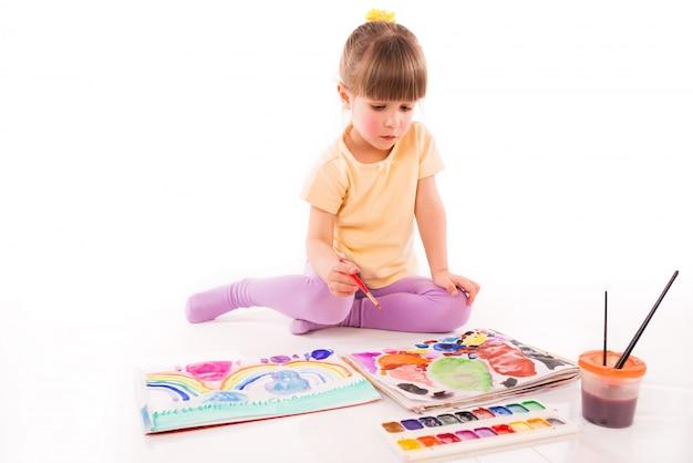 Leuk meisje zit op de vloer en tekent